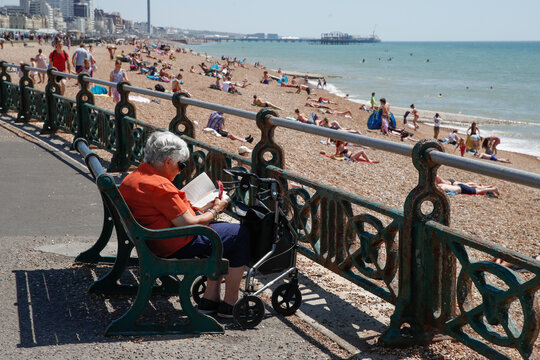 A woman reads a book by the sea, as the spread of the coronavirus disease (COVID-19) continues, in Brighton