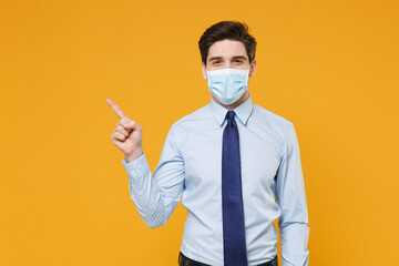 Smiling young business man in blue shirt tie sterile face mask isolated on yellow background. Epidemic pandemic coronavirus 2019-ncov sars covid-19 flu virus concept. Pointing index finger aside up.