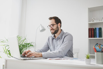 Smiling young bearded business man in gray shirt glasses sitting at desk in light office on white wall background. Achievement business career concept. Working on laptop pc computer, holding pen.