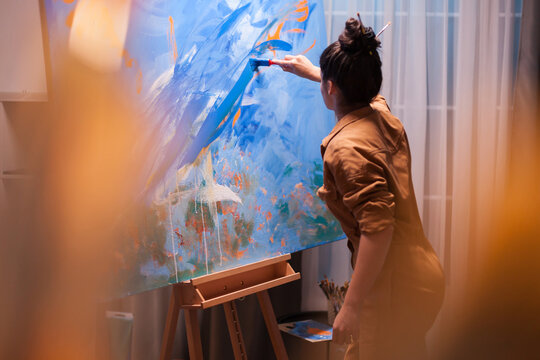 Motivated young painter making a masterpiece in art studio. Modern artwork paint on canvas, creative, contemporary and successful fine art artist drawing masterpiece