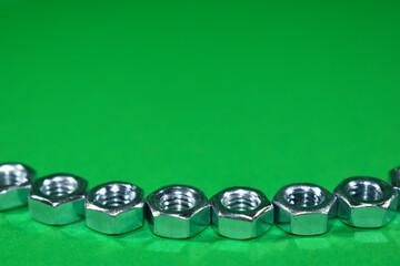 Metalowe nakrętki na zielonym tle. - fototapety na wymiar
