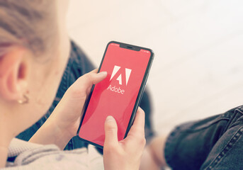 KYIV, UKRAINE-JANUARY, 2020: Adobe on Mobile Phone Screen. Young Girl Pointing or Looking on Adobe Site During a Pandemic Self-Isolation and Coronavirus Prevention.