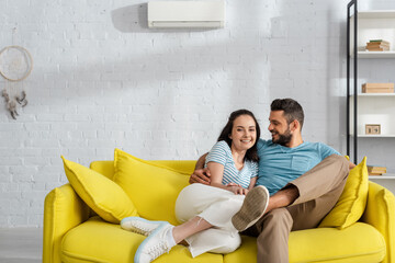 Handsome bearded man embracing smiling girlfriend on couch in living room