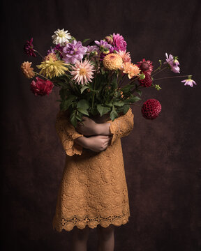 Classic studio portrait of girl in yellow dress holding lots of colorful autumn flowers in her arms,, hiding her face