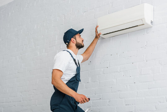 Side view of workman in workwear holding screwdriver near air conditioner