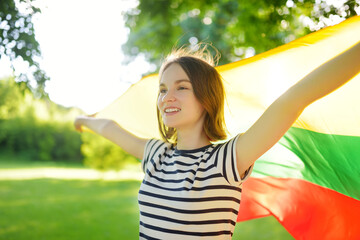 Cute young girl holding tricolor Lithuanian flag on Lithuanian Statehood Day.