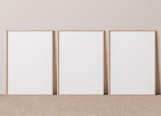 Blank vertical poster frame mock up standing on beige floor. Three wooden frames isolated in Scandinavian interior. 3d render
