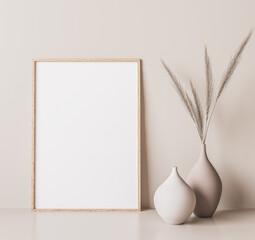 Obraz Vertical wooden frame mock up. Wooden frame poster, and simple vase with pampas on beige wall. 3D illustrations. - fototapety do salonu