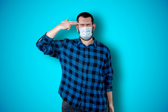 Portrait of a puzzled bearded man holding hands on his head isolated over blue background using mask. Coronavirus concept