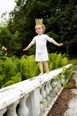 Little girl walking on a balustrade wearing cardboard crown