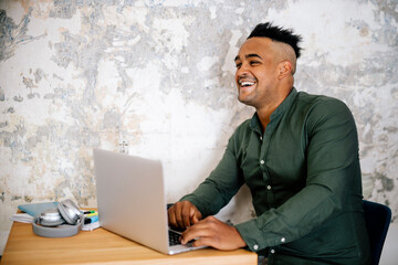 Portrait of laughing young man working on laptop at home office