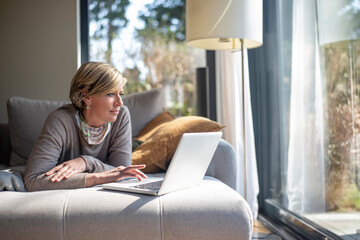 Mature woman using laptop while lying on sofa in living room during working from home