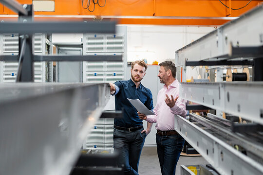 Two men discussing a plan in a factory
