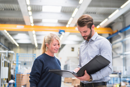 Man with a folder and woman in a factory