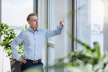 Businessman looking out of window in office