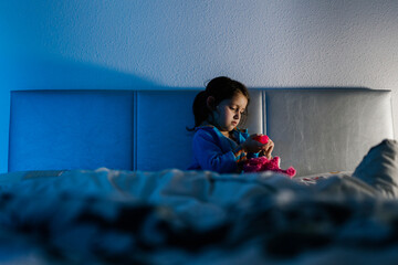Little girl sitting on bed playing with her toy
