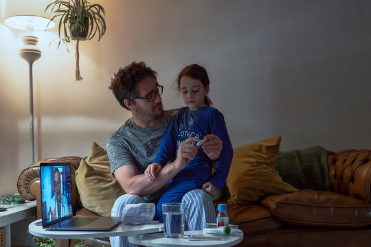 Man holding thermometer while sitting with sick daughter during video call at home