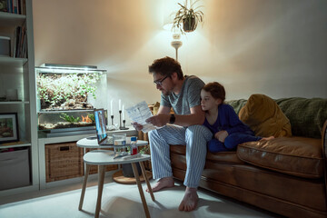 Sick girl sitting by father holding prescription while discussing with doctor over video call at home