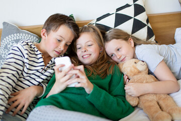 Group picture of three children lying together on bed looking at cell phone