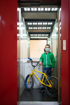 Full length portrait of boy with bicycle standing in elevator