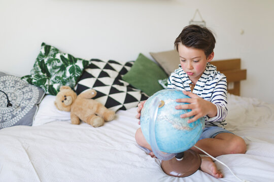 Portrait of little boy sitting on bed with his globe