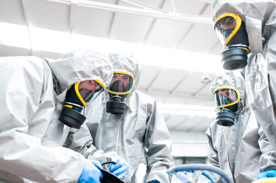 Low angle view of sanitation workers preparing for decontamination in warehouse