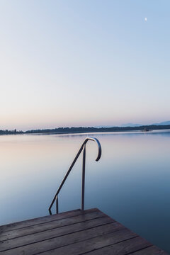Germany, Bavaria, Prien am Chiemsee, Handrail and steps leading into Chiemsee lake at dawn