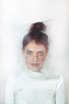 Portrait of redheaded young woman wearing transparent mask with question