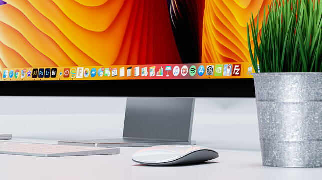 MacOS Catalina dock on professional monitor next to magic mouse and keyboard made by Apple. All in focus