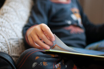Close up of child's hand turning page of book