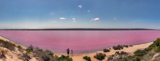 Pano of couple standing on shore of Hutt Lagoon / Pink Lake created by carotenoid-producing algae