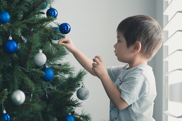 Cute mixed race boy hanging decorations on Christmas tree