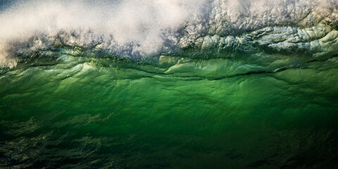 Wave breaking in big surf, green water backlit by sunrise