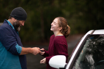 Father handing car keys to teenaged daughter
