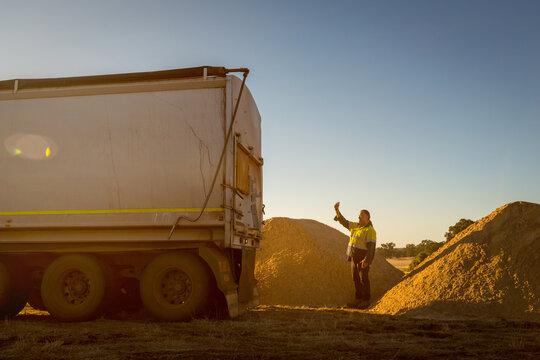 Worker directing reversing truck
