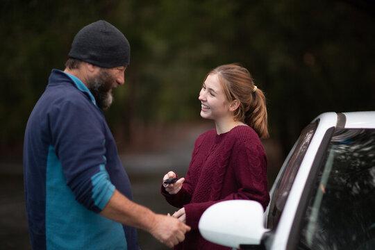 Teen girl taking car keys from her dad