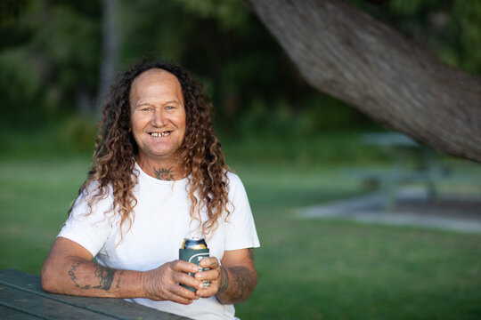 smiling middle-aged man holding drink outdoors in park