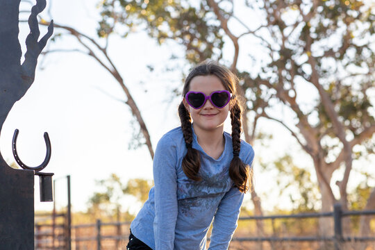 Young girl with plaits and sunglasses