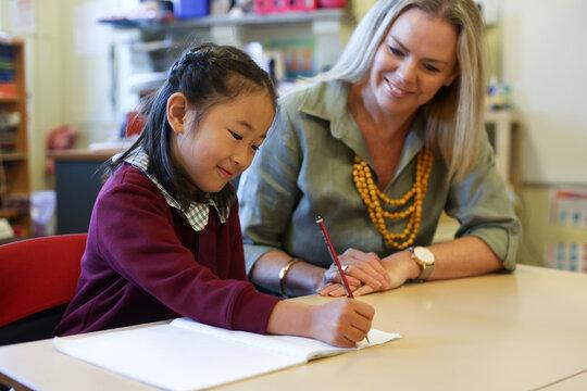 Teacher helping child with  their school work