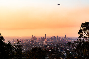 View of Brisbane City skyline with colourful orange smoke haze and airplane  in the sunset