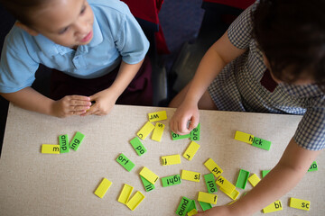 Two primary school girl students collaborating with coloured word tiles