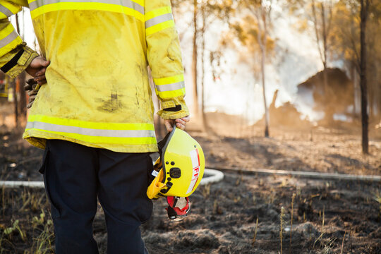 Fire fighter standing beside burnt grass holding safety helmet in hand