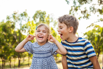 Kids being silly together - boy shouting and roaring at little girl with ears blocked not listening