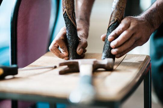 Hands of an Aboriginal Artist with Message Sticks