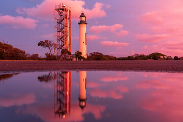 A lighthouse and its reflection against a colourful sunset sky