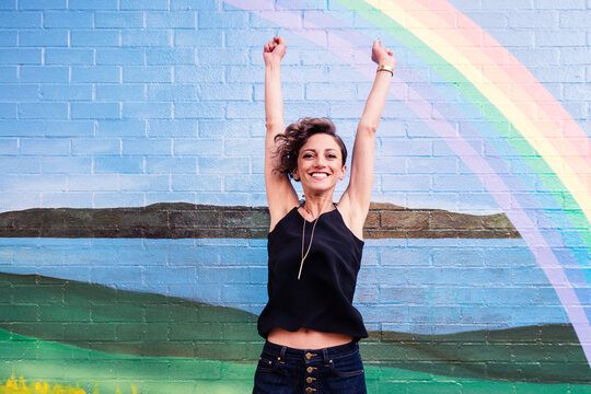 happy woman in front of brick wall with rainbow mural