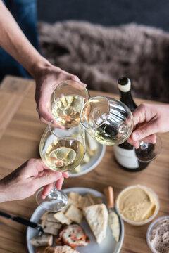 wine toast, three people clinking glasses