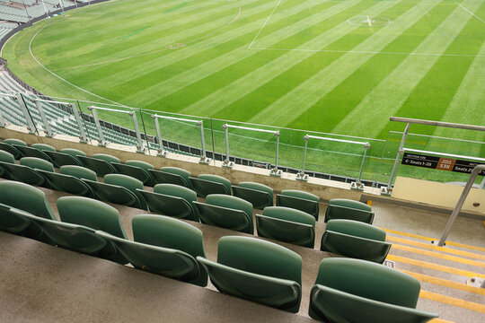 Empty stadium seats and a green afl oval