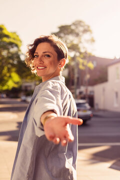 woman reaching back with hand out