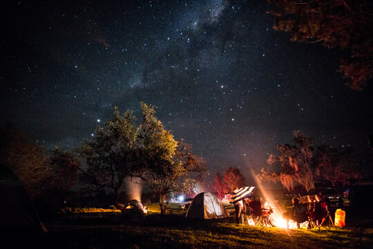 Family camping under starry sky at night